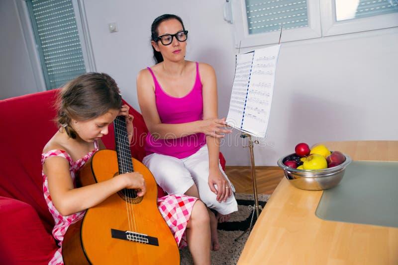 Menina nova do preteen que tem a lição da guitarra em casa fotografia de stock