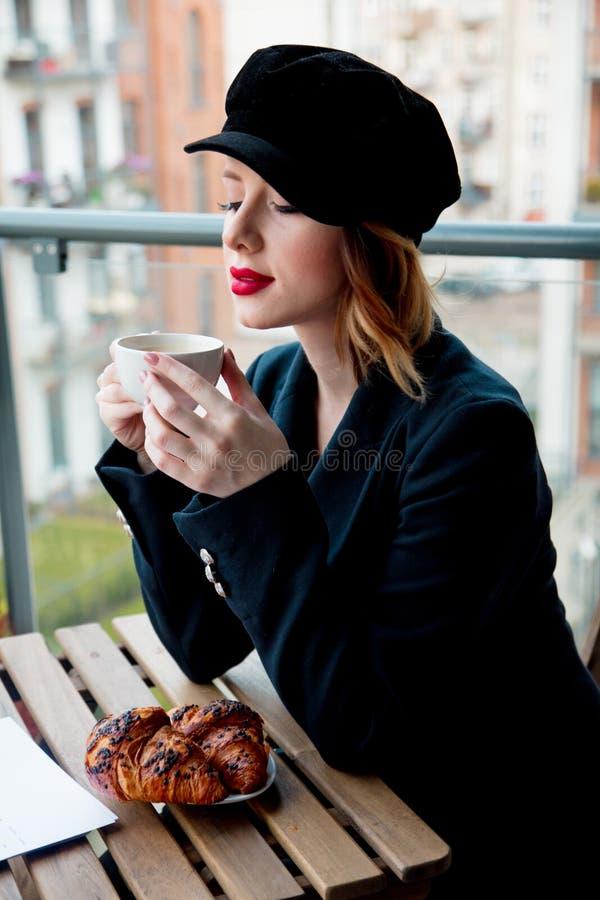 A menina nova do redehad na roupa preta tem um café da manhã fotografia de stock royalty free