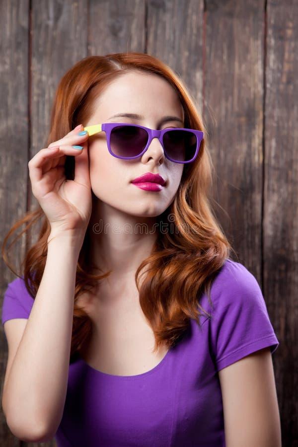 Menina nova do redehad nos óculos de sol foto de stock