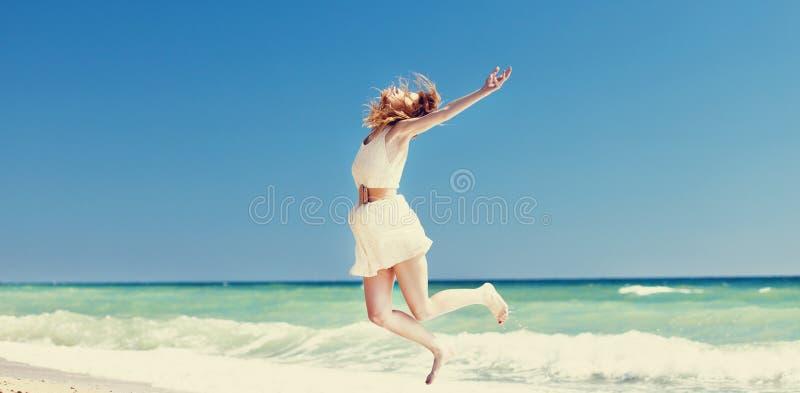 Menina nova do redhead que salta na praia. fotos de stock royalty free