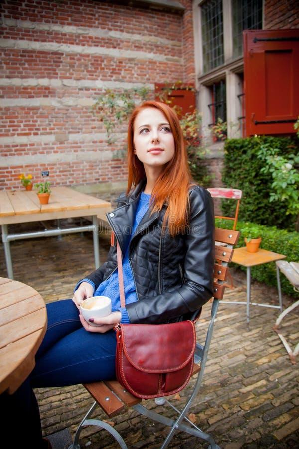 Menina nova do ruivo no chapéu em um café em Amsterdão foto de stock royalty free