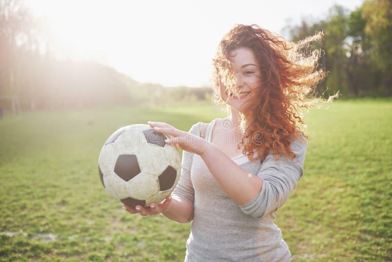 Menina nova do ruivo no jogador ocasional no estádio de futebol no por do sol imagens de stock royalty free