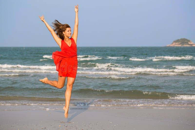 Menina nova do ruivo que salta na praia fotos de stock