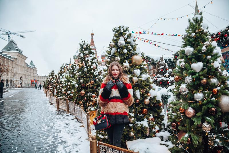 Menina nova do russo no quadrado vermelho com o feriado de inverno no levantamento de Moscou, à moda e bonito próximo à árvore de imagens de stock royalty free