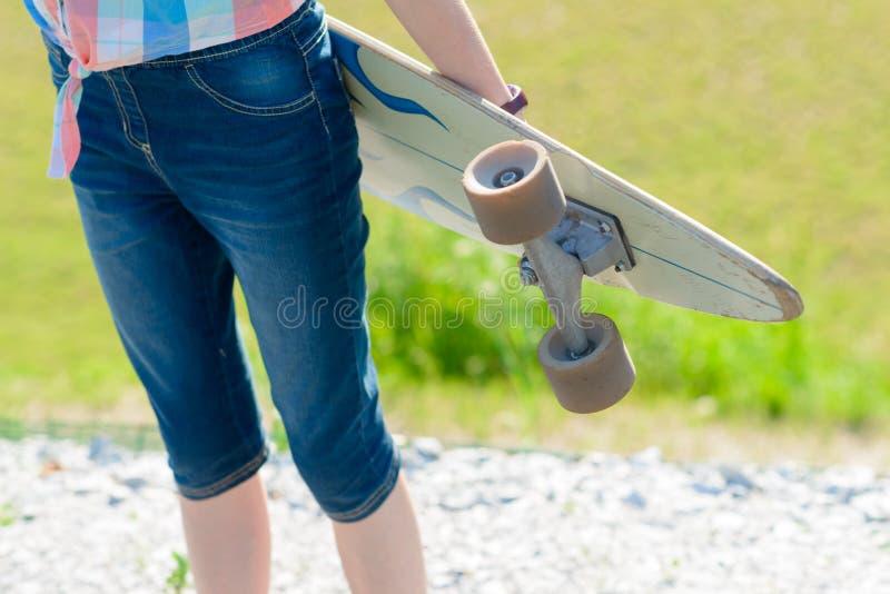 Menina nova do skate que guarda seu longboard fora no por do sol fotos de stock royalty free
