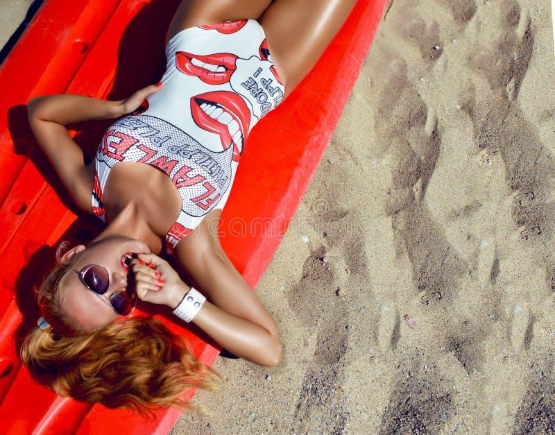 Menina nova do surfista com o 'sexy' no biquini e em sunglass 'sexy' do corpo do ajuste foto de stock royalty free