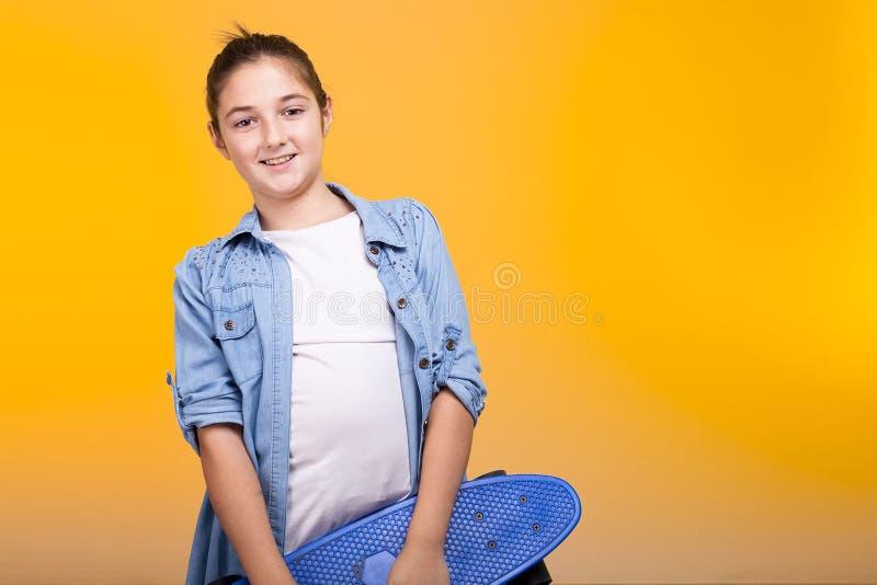 Menina nova do teeanger que guarda um skate azul em suas mãos fotografia de stock