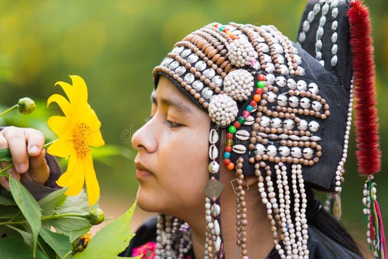 A menina nova do tribo do monte do sorriso bonito nos girassóis jardina fotografia de stock royalty free
