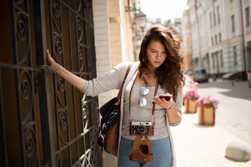 Menina nova do turista que olha em seu telefone ao andar na rua imagens de stock royalty free