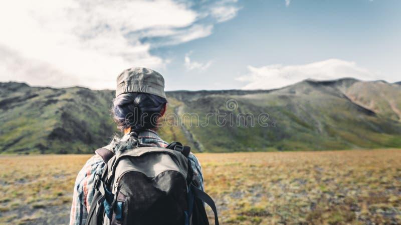 A menina nova do viajante com trouxa é contratada na caminhada nas montanhas, vista traseira Conceito do estilo de vida da aventu imagem de stock royalty free