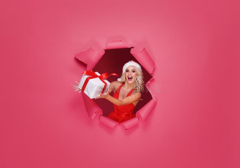 Menina nova e bonita de Santa em um conceito do Natal Fundo vermelho com um furo no papel fotografia de stock