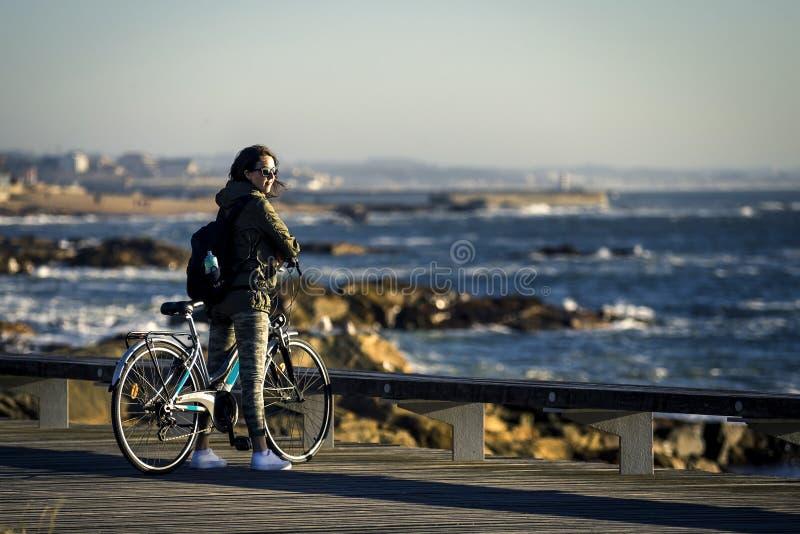 A menina nova e bonita está montando uma bicicleta pelo cais ao lado do Oceano Atlântico imagem de stock royalty free