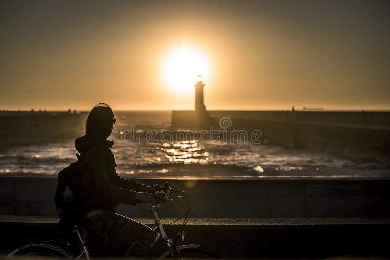 A menina nova e bonita está montando uma bicicleta pelo cais ao lado do Oceano Atlântico fotografia de stock royalty free