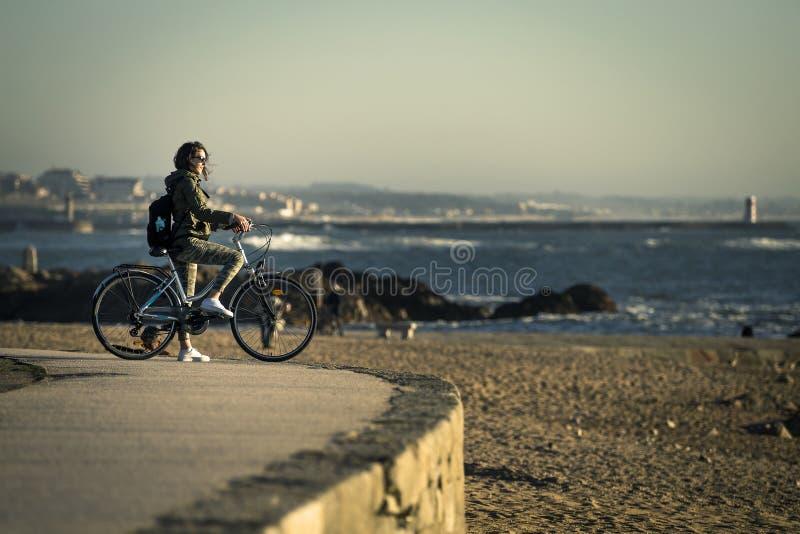 A menina nova e bonita está montando uma bicicleta pelo cais ao lado do Oceano Atlântico imagem de stock