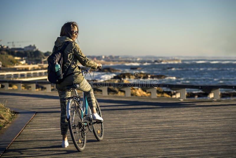 A menina nova e bonita está montando uma bicicleta pelo cais ao lado do Oceano Atlântico fotografia de stock