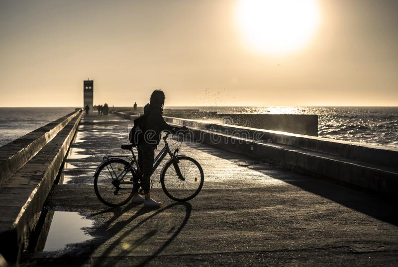 A menina nova e bonita está montando uma bicicleta pelo cais ao lado do Oceano Atlântico imagens de stock