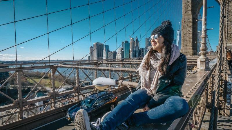A menina nova e imprudente senta-se na borda da ponte de Brooklyn New York imagens de stock royalty free