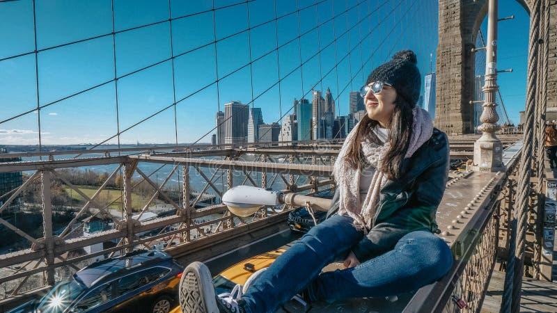 A menina nova e imprudente senta-se na borda da ponte de Brooklyn New York imagem de stock royalty free