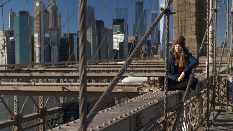 A menina nova e imprudente senta-se na borda da ponte de Brooklyn New York imagem de stock
