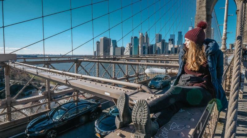 A menina nova e imprudente senta-se na borda da ponte de Brooklyn New York fotografia de stock royalty free