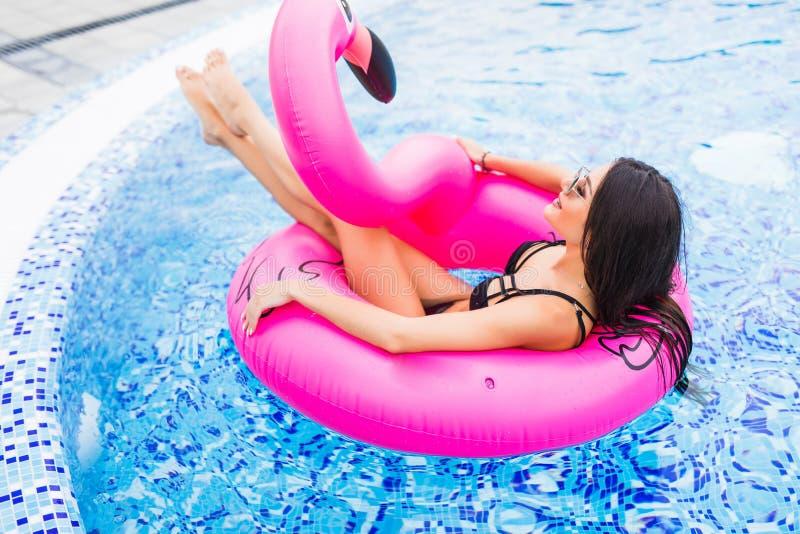 Menina nova e 'sexy' que tem mentiras no sol um colchão cor-de-rosa gigante inflável do flutuador da associação do flamingo com u fotos de stock