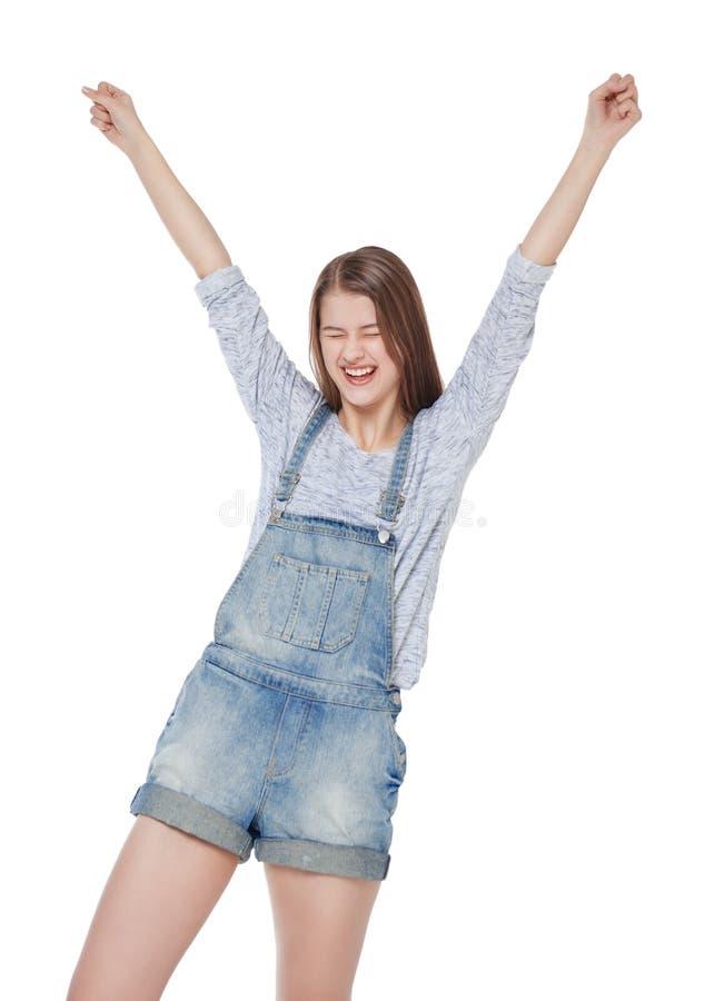 A menina nova feliz da forma em macacões das calças de brim com mãos isola-se acima imagens de stock royalty free
