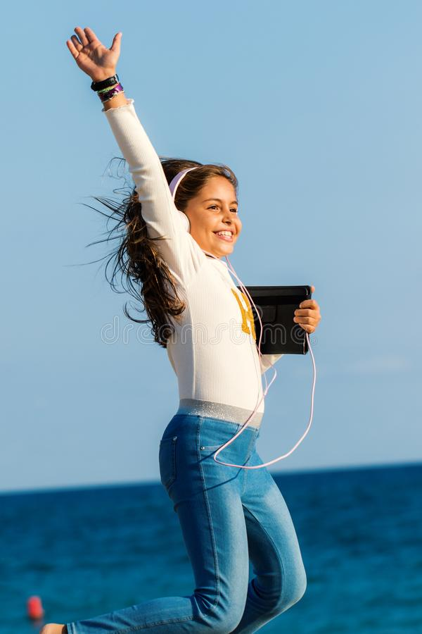 Menina nova feliz do tween que salta com fones de ouvido e tabuleta na praia fotografia de stock royalty free