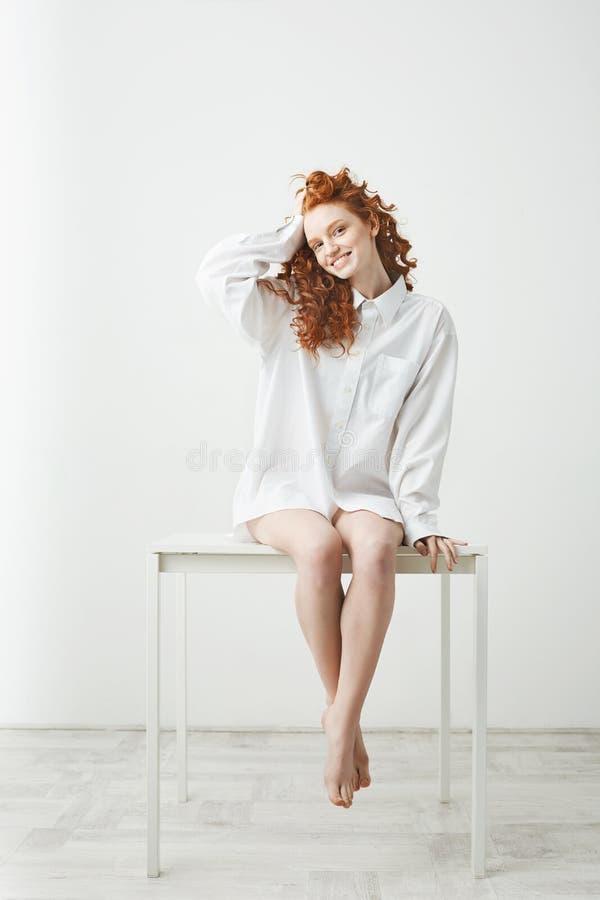 Menina nova macia do ruivo na camisa que senta-se na tabela sobre o fundo branco que sorri olhando a câmera que corrige o cabelo imagem de stock