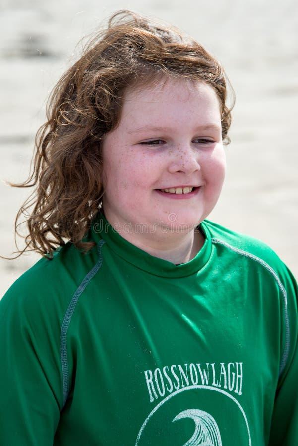 Menina nova na praia que toma lições surfando imagem de stock