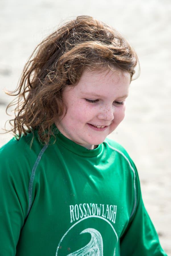 Menina nova na praia que toma lições surfando foto de stock