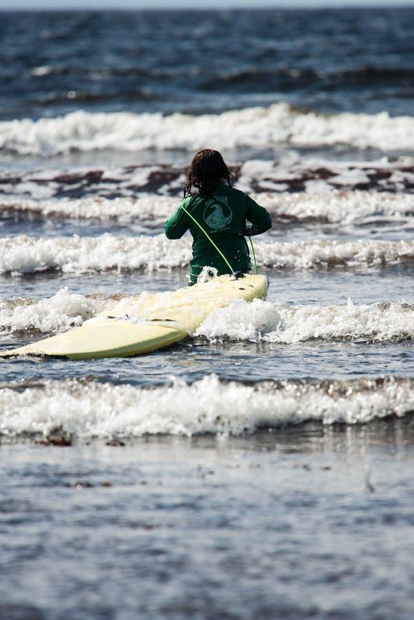 Menina nova na praia que toma lições surfando foto de stock royalty free