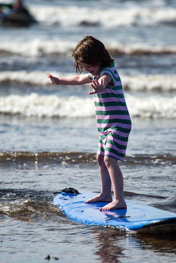 Menina nova na praia que toma lições surfando fotografia de stock royalty free