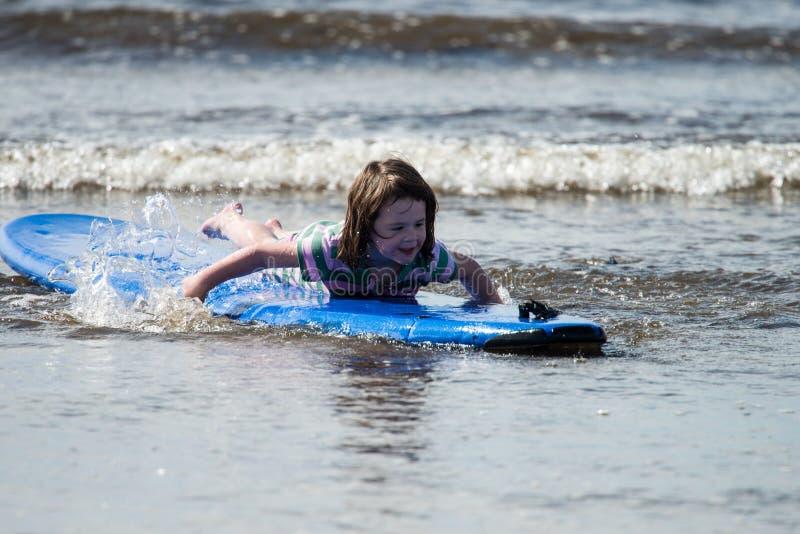 Menina nova na praia que toma lições surfando imagens de stock royalty free