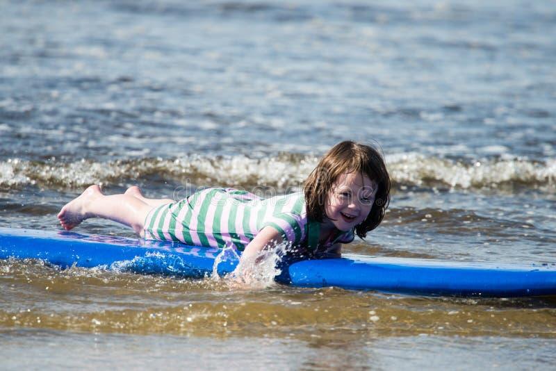 Menina nova na praia que toma lições surfando imagens de stock