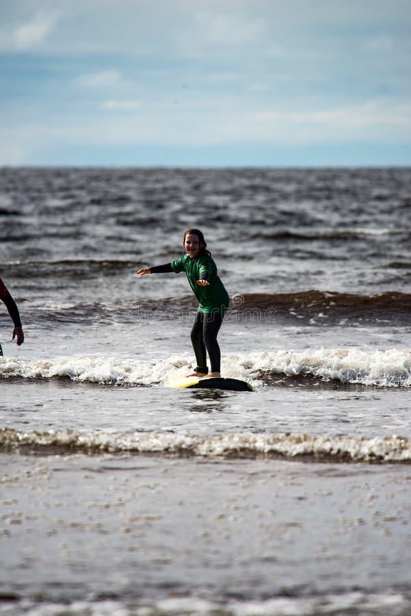 Menina nova na praia que toma lições surfando fotos de stock royalty free