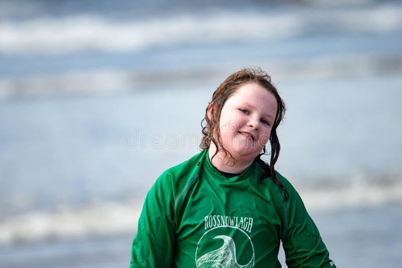 Menina nova na praia que toma lições surfando imagem de stock royalty free