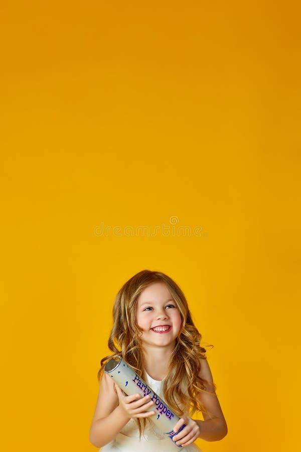 Menina nova que tem o divertimento com confetes sobre o fundo amarelo Conceito do divertimento e do estilo de vida imagens de stock royalty free