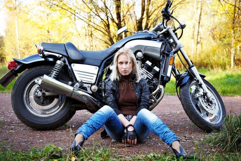 A menina o assento louro sobre um motorc fotos de stock