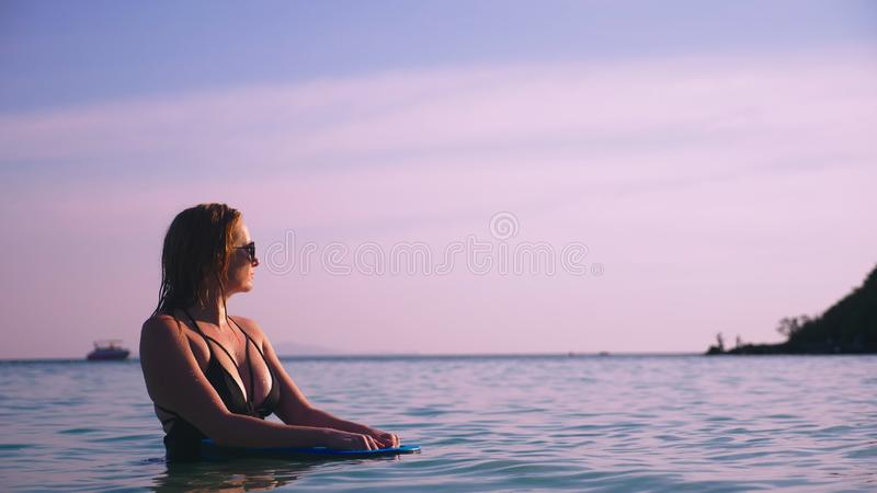 A menina o louro em um maiô preto e em uns vidros pretos Um modelo bonito com um corpo 'sexy' nada guardar imagem de stock royalty free