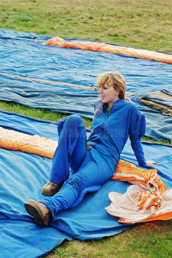 A menina o parachutist na obscuridade - macacões azuis fotografia de stock