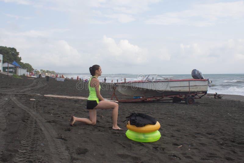 A menina, o powerboat e o amarelo, anel de flutuação verde na praia, nublado, nuvens, acenam imagens de stock