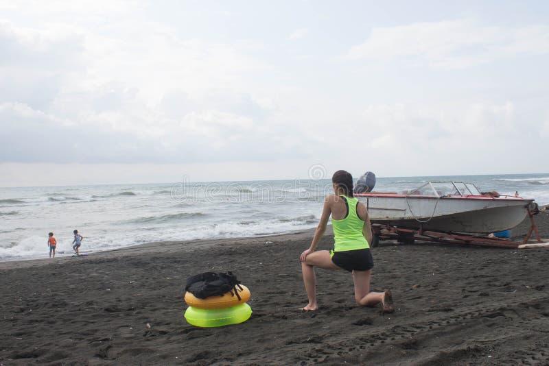A menina, o powerboat e o amarelo, anel de flutuação verde na praia, nublado, nuvens, acenam fotografia de stock royalty free