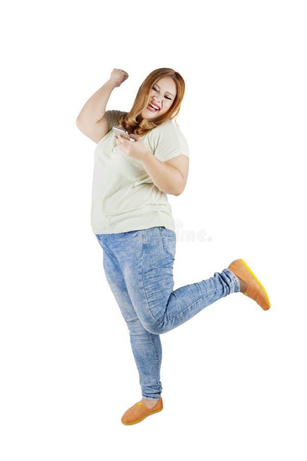 A menina obeso alegre lê a mensagem dos sms fotografia de stock royalty free