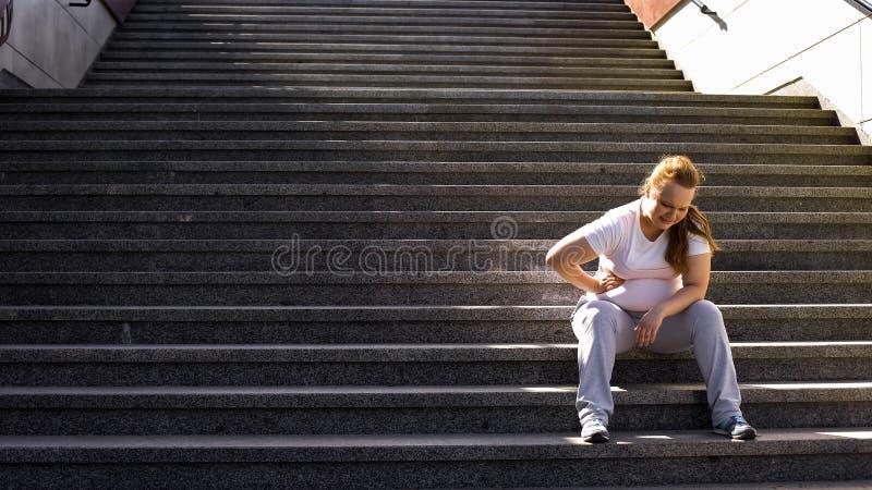 A menina obeso sente dores laterais depois que exercícios árduos fora, dor no fígado foto de stock royalty free