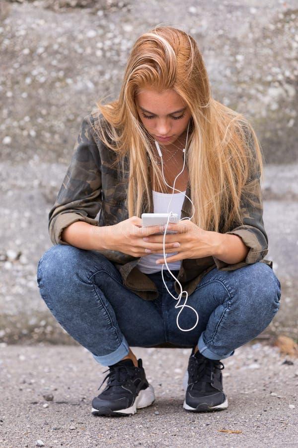 A menina obstruiu em seu telefone celular fotos de stock royalty free