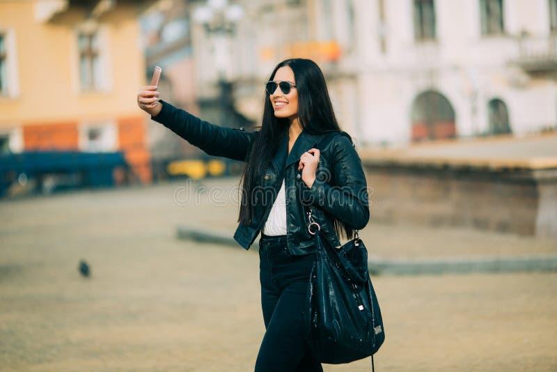 A menina ocasional bonita nova toma um selfie em seu telefone celular fotos de stock royalty free
