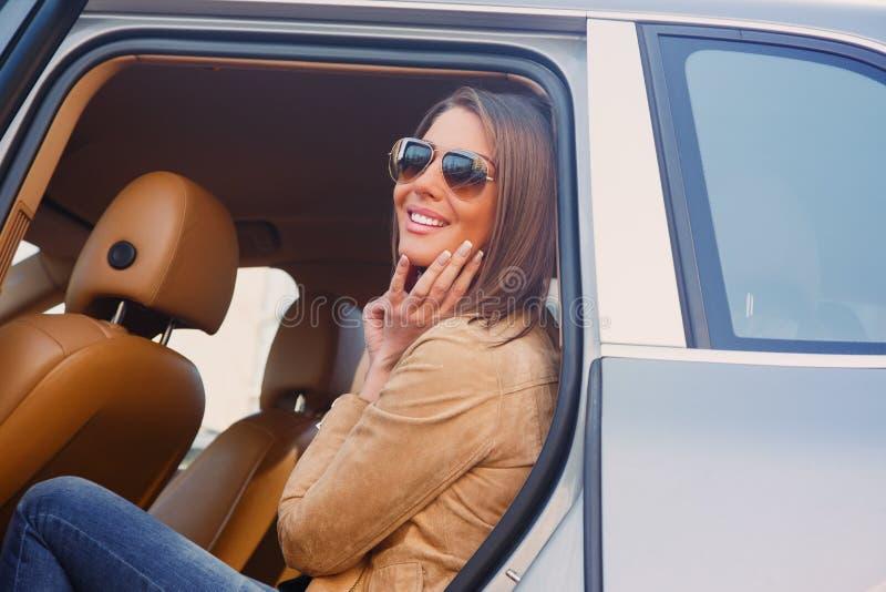Menina ocasional de sorriso em um carro imagens de stock royalty free