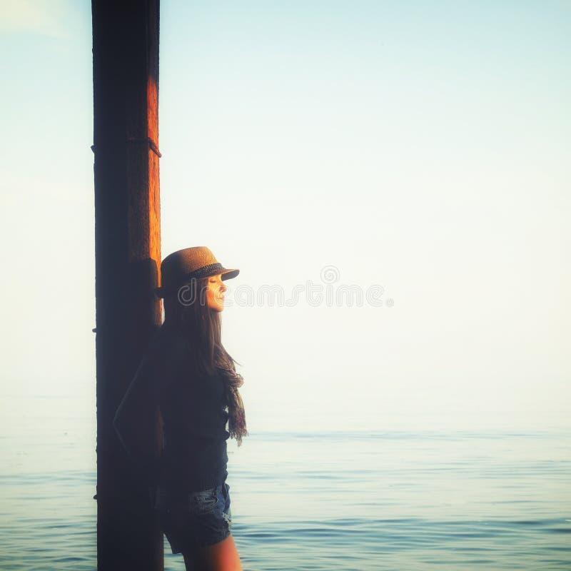 A menina ocasional que relaxa sob o cais em uma água do mar, aprecia a luz do por do sol e o ar de respiração imagem de stock
