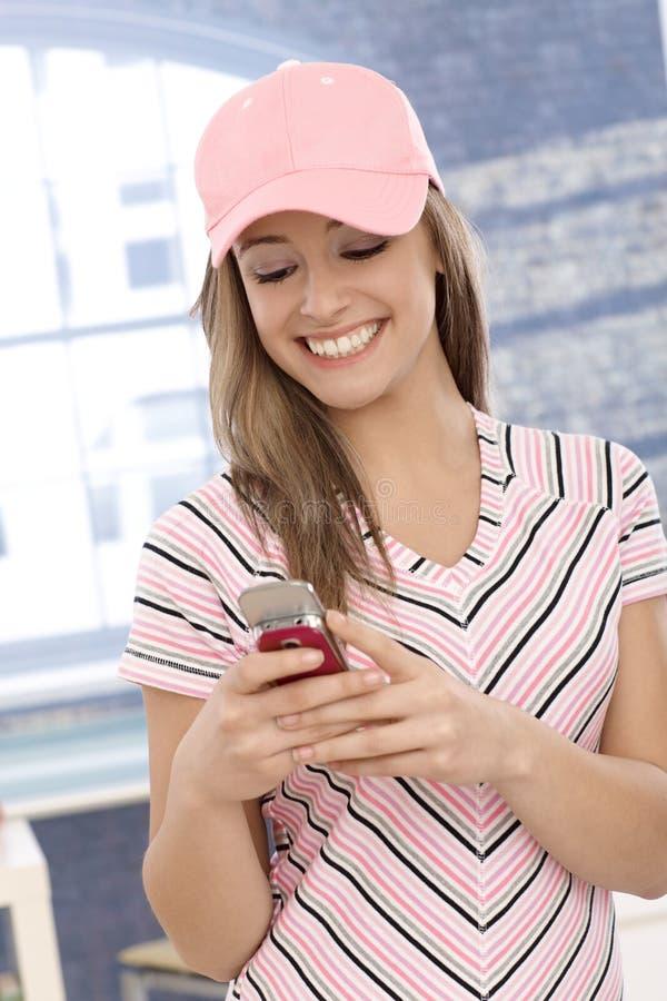 Menina ocasional que usa o sorriso do telemóvel imagem de stock