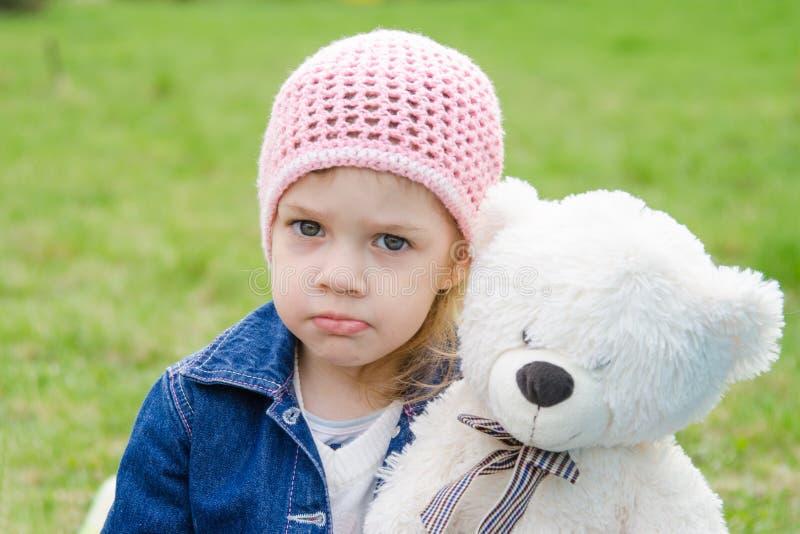 Menina ofendida com um piquenique do urso de peluche imagens de stock royalty free